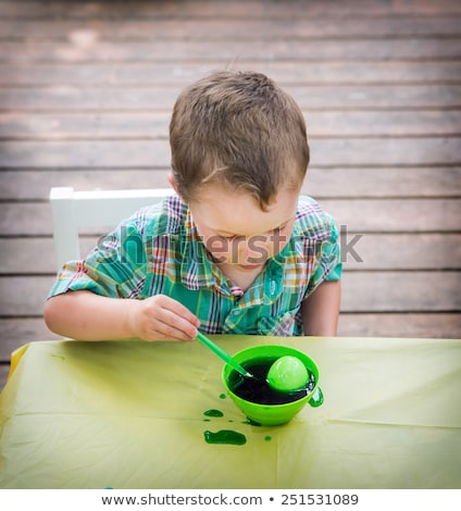 family decorating easter eggs on table outdoors stock photo © monkey_business