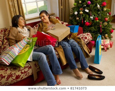 Foto stock: Hispanic Mother And Daughter Resting After Christmas Shopping