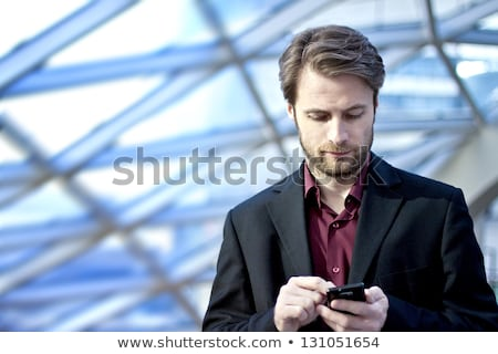 Businessman using cell phone office building lobby Stock photo © HASLOO