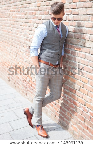 man leaning on brick wall looking down stock photo © feedough