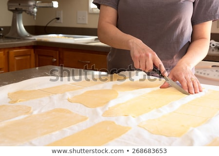 Chef trimming rolled pasta dough in a kitchen Stock photo © ozgur