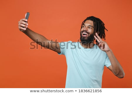 young boy talking on mobile and showing the victory sign stock photo © feedough