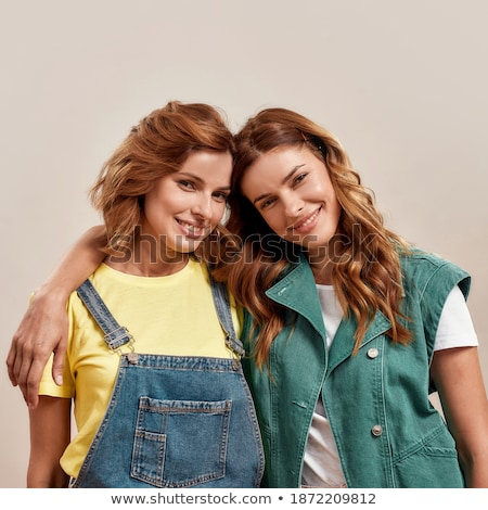 two beautiful sisters twins standing and hugging together stock photo © deandrobot