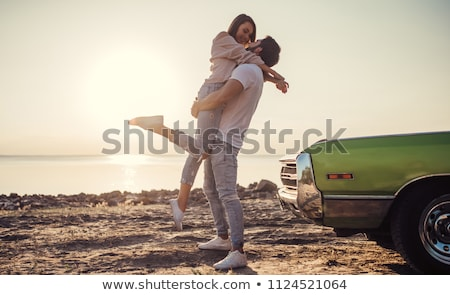 happy young hipster couple standing at the beach and hugging stock photo © deandrobot