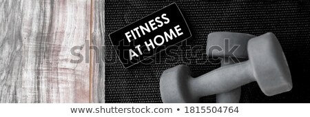 gym fitness mat with free weights mobile phone app stock photo © maridav