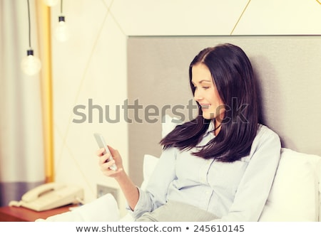 happy businesswoman with smartphone in hotel room stock photo © dolgachov