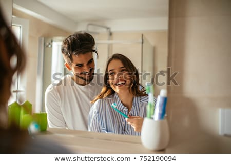 couple in bathroom brushing teeth stock photo © monkey_business