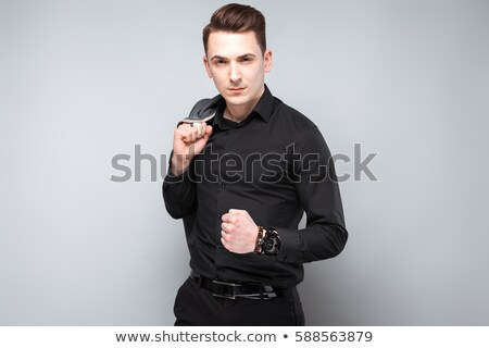 attractive young businessman in black jacket costly watch and black shirt stock photo © traimak