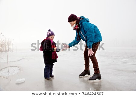 Girl and boy iceskating on frozen lake Stock photo © IS2