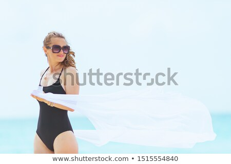 woman in bikini and sunglasses with pareo on beach stock photo © dolgachov