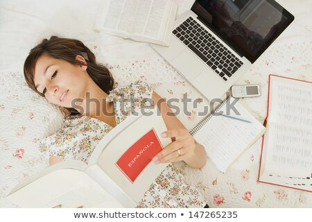 Female student lying in bed, learning Stock photo © IS2