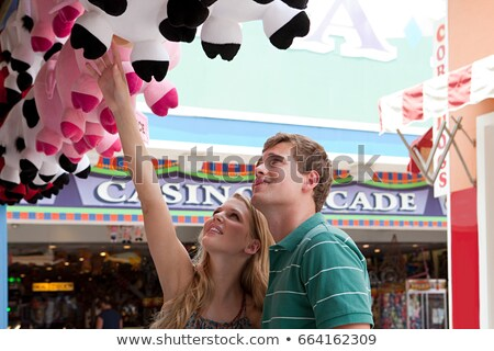 Teenage couple looking at teddy bears at fun fair Stock photo © IS2