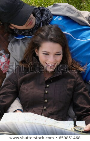 woman smiling holding map reclining stock photo © is2