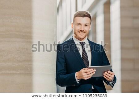 Mosolyog fiatal férfi menedzser hivatalos tart Stock fotó © deandrobot