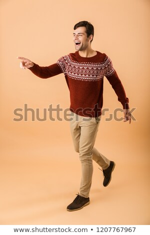 Foto d'archivio: Full Length Image Of Cheerful Man 20s With Bristle Wearing Knitt