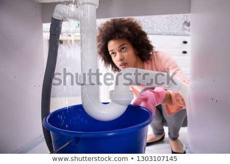woman looking at water leaking from sink pipe stock photo © andreypopov