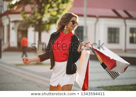 Fashionable brunette girl with colorful paper shopping bags, walking at street.  Stock photo © studiolucky