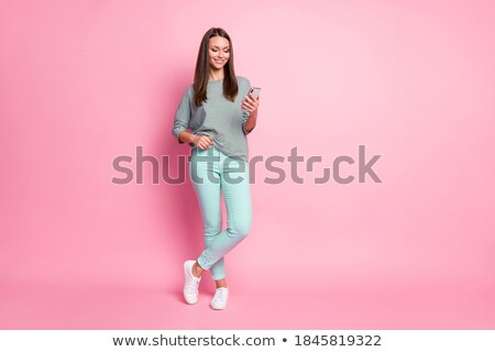Young stylish woman in white trousers, sneakers and striped pullover Stock photo © pressmaster