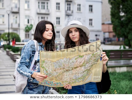 two young traveler with backpack are holding map relaxing and t stock photo © freedomz
