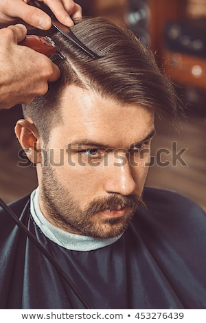 The hands of young barber making haircut to attractive man in ba Stock photo © ruslanshramko