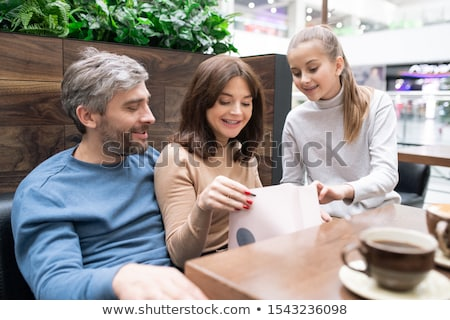 young woman taking look at gift in paperbag with daughter and husband near by stock photo © pressmaster