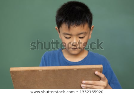 Front view of Asian schoolboy writing on chalk slate against green chalkboard in a classroom at elem Stock photo © wavebreak_media