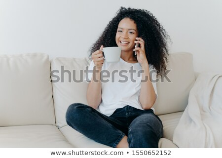 Cheerful Afro American woman has coffee break in living room, sits on couch, calls friend via modern Stock photo © vkstudio