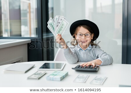 Little accountant with toothy smile holding bunch of dollar banknotes over desk Stock photo © pressmaster