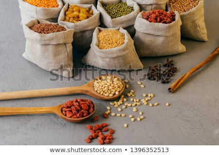 Shot of small bags with colorful cereals, nutritious legumes, star anise near, two wooden spoons wit Stock photo © vkstudio