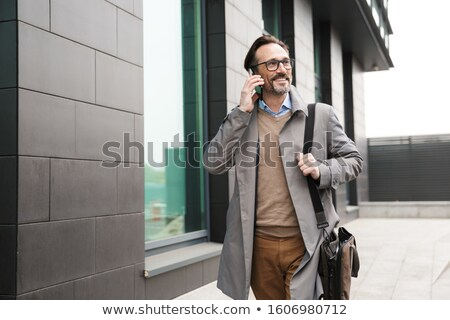 Image of bearded adult man in jacket smiling and walking in park Stock photo © deandrobot