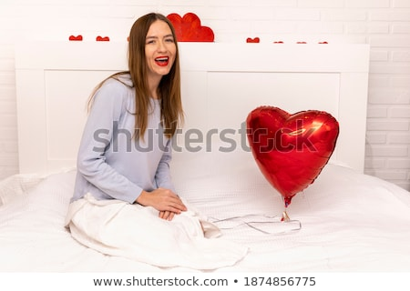Portrait of young beautiful awake woman with gifts on bed at bed stock photo © HASLOO