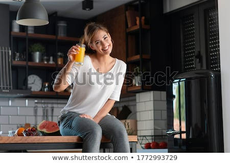 Young woman holding a glass of orange juice Stock photo © photography33