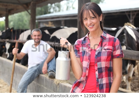 Woman with a churn of milk in front of a herd of cows Stock photo © photography33