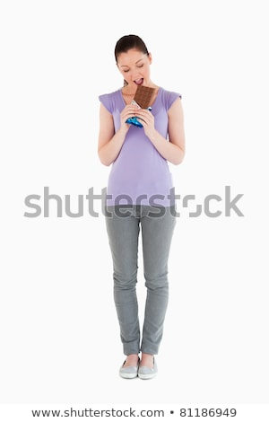 Portrait of a beautiful woman eating a chocolate block while standing against a white background stock photo © wavebreak_media