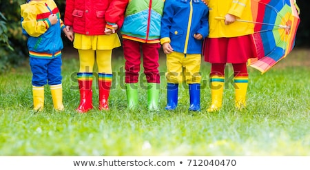 little girl wearing rubber boots on lawn Stock photo © phbcz