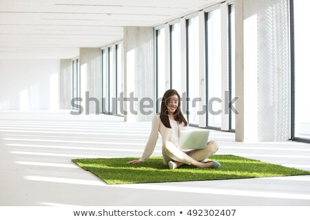 Woman sitting on carpet using laptop Stock photo © AndreyPopov