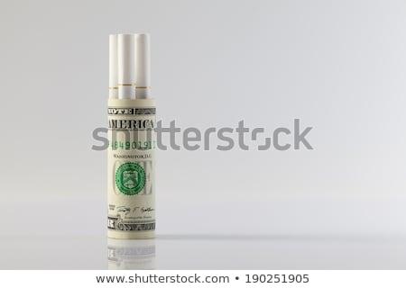 Rolls of dollar bills and a long cigarettes Stock photo © CaptureLight