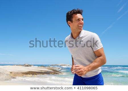 Handsome good-looking man on beach smiling happy Stock photo © Maridav