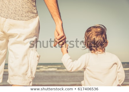 father and children looking to sea from beach stock photo © monkey_business