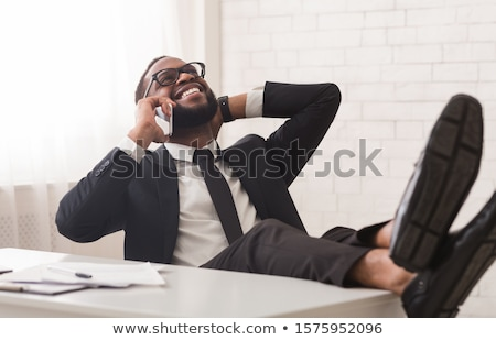 Handsome young business man leaning on a white table Stock photo © feedough