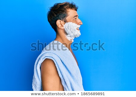 Side view portrait of handsome man with foam on face Stock photo © deandrobot
