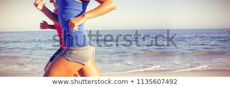 happy young couple running in sea at beach stock photo © wavebreak_media