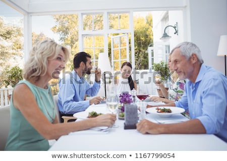 Happy friends interacting with each other while having meal Stock photo © wavebreak_media