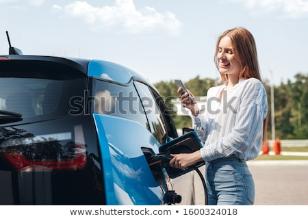 Jeune femme permanent voiture électrique femme technologie amusement Photo stock © IS2