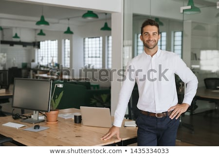 Businessman standing at table Stock photo © IS2