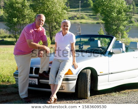 senior woman leaning on car by river stock photo © is2