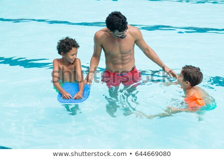 Father interacting with kids in the pool Stock photo © wavebreak_media