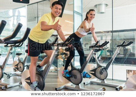 Cheerful couple showing thumbs up during indoor cycling Stock photo © Kzenon