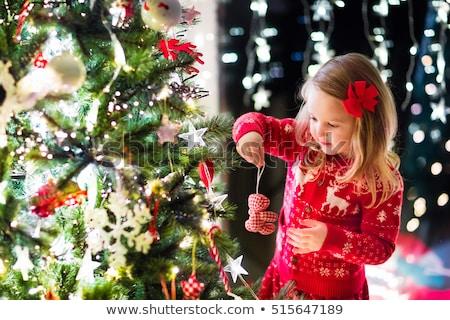happy girl in red dress decorating christmas tree Stock photo © dolgachov