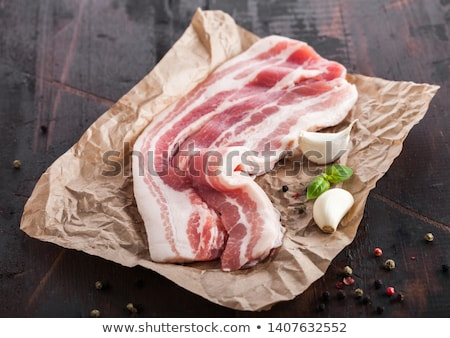 Raw fresh smoked pork bacon slices on butchers paper on dark wooden board with garlic basil. Stock photo © DenisMArt